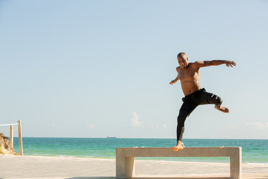 Man jumping a bench at the beach