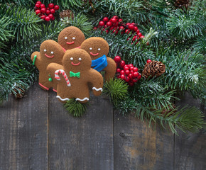 Ginger men cookies with christmas tree branches on old wooden background.