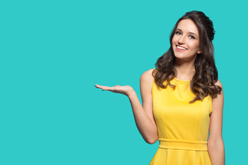 Fashion bright woman holds out her hand to the empty space. Woman in a yellow dress on a turquoise background