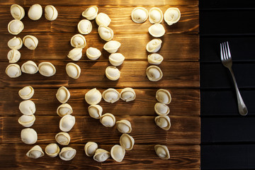 Eat us. Letters from dumplings on dark and light boards. Country style. Russian dish
