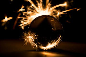 Burning sparkler behind a glass ball.