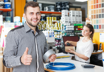 Male with purchases holding thumb up in tools store, woman working