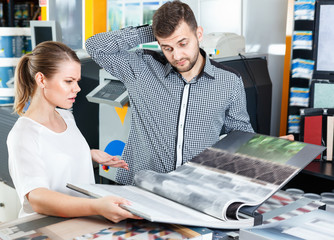 Young couple choosing wallpaper from samples at magazine in household shop