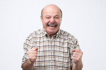 Senior handsome man laughing and looking at camera with a big grin. He is so happy to find out about his pension savings