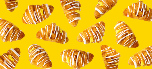 Croissants with white cream flying over yellow background. Delicious sweet food falling. Panorama view