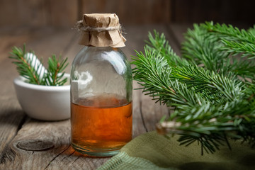 Fir aromatic oil. Pine essential oil in a transparent glass bottle. Coniferous tree branches and mortar.