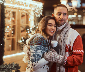 A young romantic couple wearing warm clothes outdoor at Christmas time, hugging and warming with hot coffee in evening street decorated with beautiful lights.