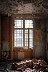 Abandoned room with flaking wallpaper