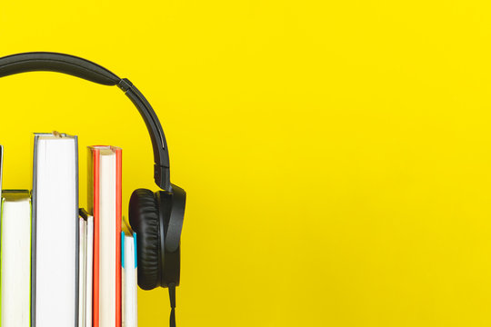 concept of audio book. headphone and books on yellow background