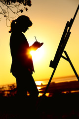 silhouette of a young woman drawing a picture on an easel on nature, female standing under tree with brush and artist's palette engaged in art at sunset