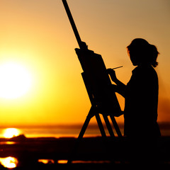 silhouette of a young woman painting a picture on an easel on nature, girl figure with brush and artist's palette engaged in art at sunset on horizon