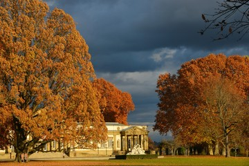 Schloss Rosenstein, Naturkundemuseum, mit Löwentor im Herbst bei Sonnenschein am Nachmittag unter dunklen Wolken in Stuttgart, Baden-Württemberg, Deutschland