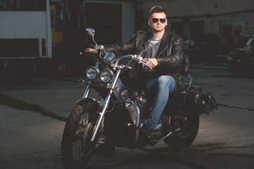 Cute biker in leather jacket is sitting on a motorcycle