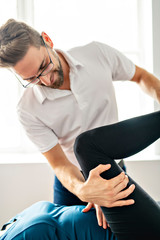 A Modern rehabilitation physiotherapy man at work with woman client working on leg