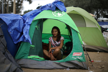 Katherine Arito, 17, who traveled alone from Honduras as part of a caravan of thousands of migrants from Central America trying to reach the United States, poses for a photo in her tent in a temporary shelter in Tijuana