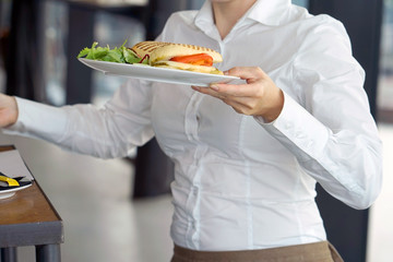 Waitress serving a client sitting at a table in a hotel restaurant, cafe. Waiter carrying a plate with an order at some festive event, party or wedding.