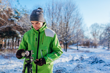 Young photographer takes pictures of winter forest using camera and tripod