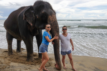 Portrait of a happy young couple with an elephant on the background of a tropical ocean beach. Tropical coast of Sri Lanka