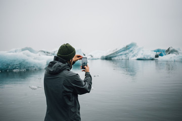 Big screen and high resolution futuristic, immersive technology smartphone, man makes photo or video of beautiful nordic landscape, ice cold ocean with floating icebergs and glaciers