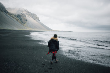 Young woman in cool outdoor outfir, red shirt and puffy down jacket walk in empty cold grey beach with black volcanic sand. Concept explore more and unconventional travels in iceland