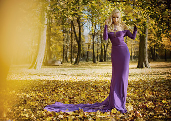 Elegant, sensual woman walking in the autumnal forest