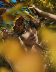Art portrait of a blond nymph posing in an autumnal park