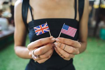 Female hands hold small flags of two countries