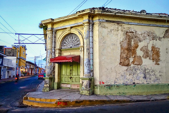 An old, weathered building with a green door and flaking paint on a corner in the city of Leon in northern Nicaragua