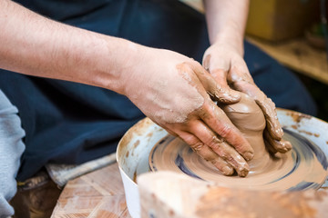 Professions Ideas and Concepts. Closeup of Hands of Male Potter Working with Clay Lump on Potter's Wheel in Workshop.