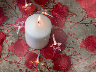 One white candle on rustic background.