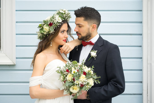 young couple bride groom getting married wedding posed photos at seaside sea beach hairpiece flowers bouquet church