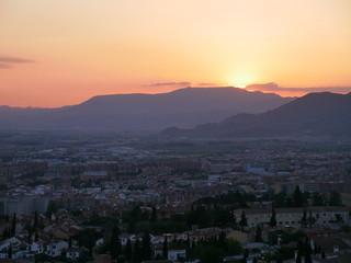 Panorama of a beautiful orange sunset over the city of Granada, Spain