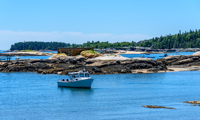 Maine Lobster Boat Anchored in a Bay in Front of a Rocky New England Coast