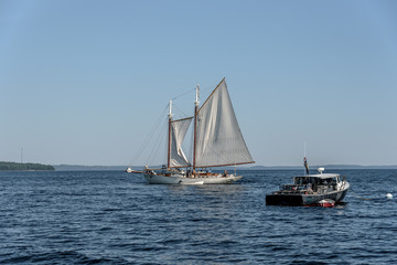 A Maine Lobster Boat Anchored Next to a Sailboat in a Bay in New England