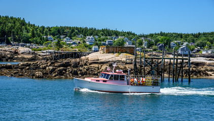 Maine Lobster Boat Leaving Port by Navigating Through the Bay and Other Anchored Lobster Boats