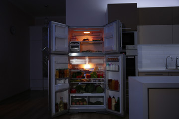 Open refrigerator filled with food in kitchen at night