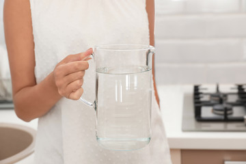 Woman holding glass jug with water in kitchen, closeup