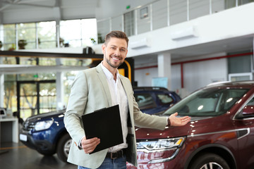 Salesman with clipboard in modern car dealership