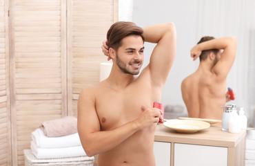 Handsome young man applying deodorant in bathroom