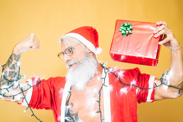 Happy tattooed santa claus equiped with white lights giving christmas gift - Trendy beard senior wearing xmas clothes and holding present - People, fun and holidays concept
