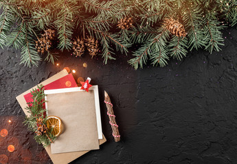 Christmas letter for Santa on dark background with pencil, fir branches, pine cones. Xmas and Happy New Year theme, bokeh, sparking, glowing. Flat lay, top view