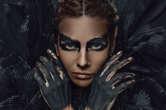 conceptual close up portrait of beautiful fashion look woman dark make up with gold