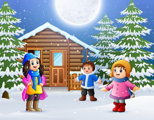 Happy kids in front of a snowy wooden house