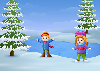 Happy kids playing in the winter landscape with frozen lake and fir trees