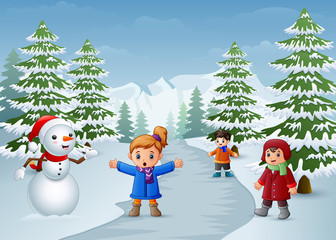 Happy kids playing with a snowman in winter