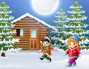 Happy kids playing in front of a snowy wooden house