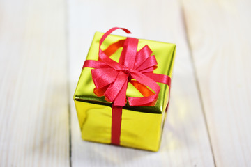 Gold gift box on wooden table