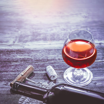 A glass of red wine on a wooden toned background with a bottle and a corkscrew.