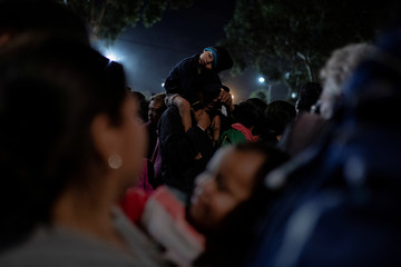 A migrant, part of a caravan of thousands from Central America trying to reach the United States, carries his baby on his shoulders before a food distribution outside a temporary shelter in Tijuana