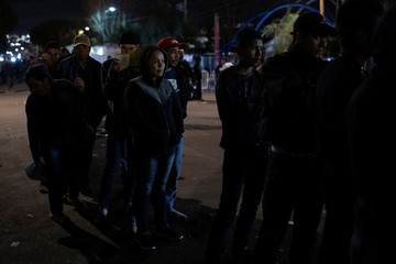 Migrants, part of a caravan of thousands from Central America trying to reach the United States, line up for a food distribution outside a temporary shelter in Tijuana